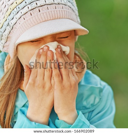 little girl in blue coat with handkerchief sneezes. - stock photo