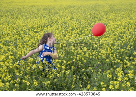 Little girl in blue dress playing with red flying balloon in yellow flowers field - stock photo