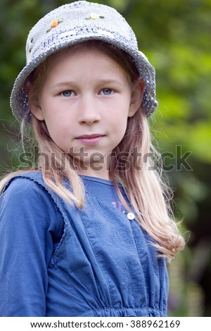 little girl in blue hat portrait on green summer background  - stock photo