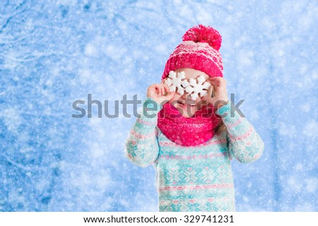 Little girl in blue knitted sweater and pink hat catching snowflakes in winter park. Kids play outdoor in snowy forest. Children catch snow flakes. Toddler kid playing outside in snow storm. - stock photo