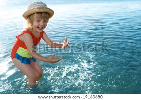 little girl in blue water sea  splashes - stock photo