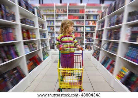 Little girl in bookshop, with cart for goods. There is one among racks. - stock photo