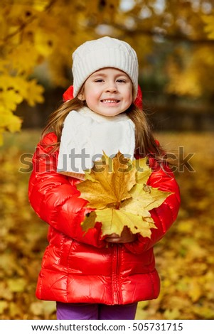 Little girl in bright clothes with leaves in their hands smiling at the park in autumn.