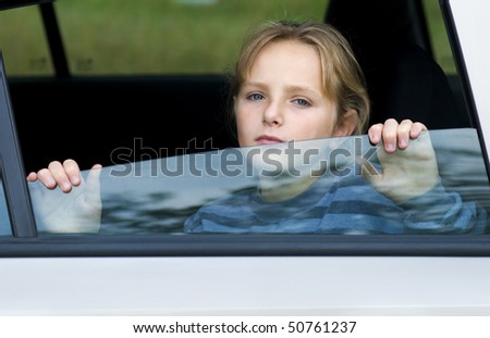 Little girl in car is going to miss her friends. - stock photo