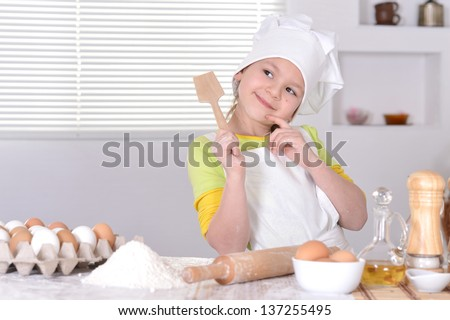 little girl in chef hat and apron  preparing  in the kitchen - stock photo