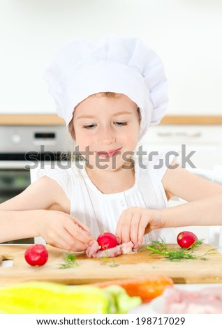 Little girl in chef hat cooking in kitchen. - stock photo