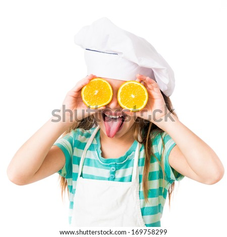 little girl in chef hat with two halves of a orange in the eyes shows tongue on a white background - stock photo