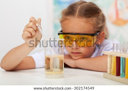 Little girl in chemistry class - stock photo