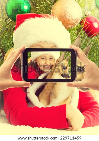 little girl in Christmas clothes holding her dog while being photographed - stock photo