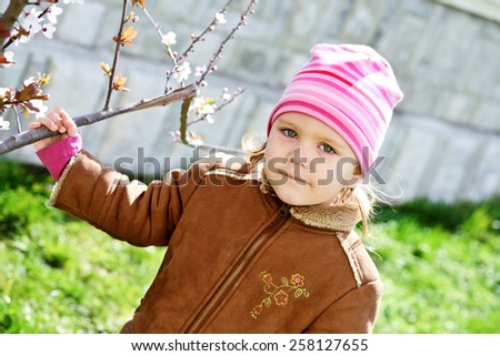 little girl in early spring with blossom tree - stock photo