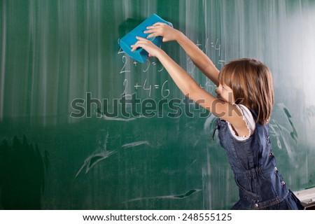 Little girl in elementary school cleaning board with sponge. Mathematics task is written on chalkboard - stock photo