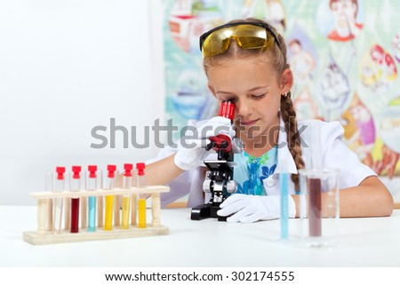 Little girl in elementary school science class using microscope - stock photo