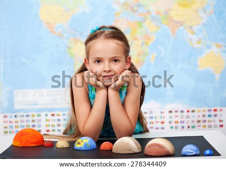 Little girl in elementary science class with her home project - the planets of our solar system - stock photo