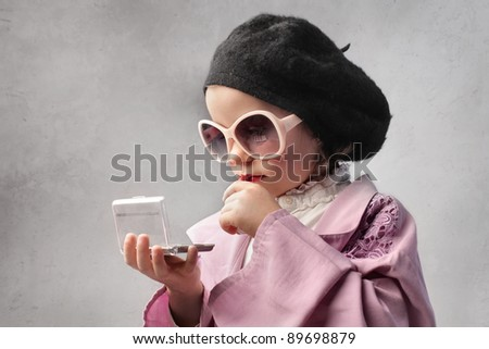 Little girl in fashion clothes looking at herself in a pocket mirror - stock photo