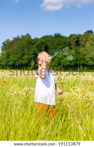 Little girl in field making soap bubbles and having fun with it - stock photo