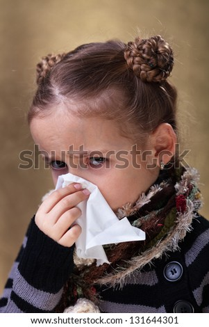Little girl in flu season - wearing warm clothes and blowing nose - stock photo