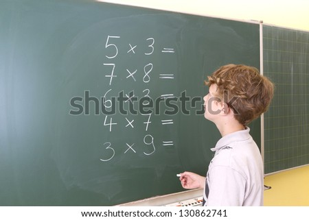 Little Girl in front of a blackboard. She is painting a triangle on the board.
