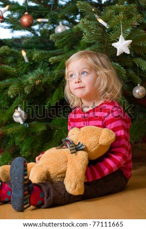 little girl in front of christmas-tree - stock photo