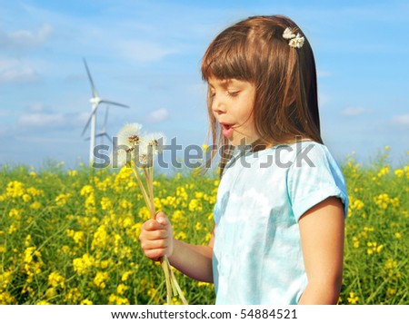 Little girl in front of windmills blowing dandelions - stock photo