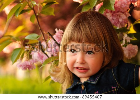 Little girl in garden, under the sakura tree. - stock photo