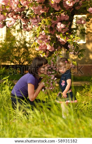 Little girl in garden with mother, under the sakura tree. Selective focus - stock photo