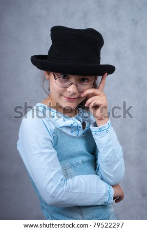 little girl in glasses and black hat looking at camera and smiling