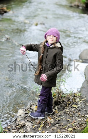 Little girl in glasses and pink hat standing by river in autumn forest