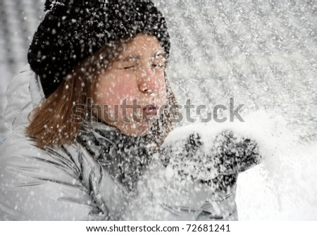 little girl in gloves and hat blowing snow on park - stock photo