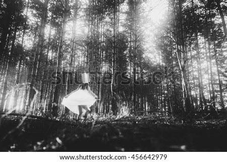 Little girl in handmade crown playing in forest