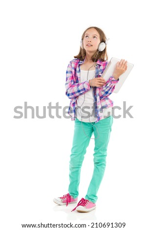 Little girl in headphones holding a digital tablet, looking up and thinking. Full length studio shot isolated on white. - stock photo