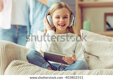 Little girl in headphones is listening to music using a tablet and smiling while sitting on sofa at home - stock photo