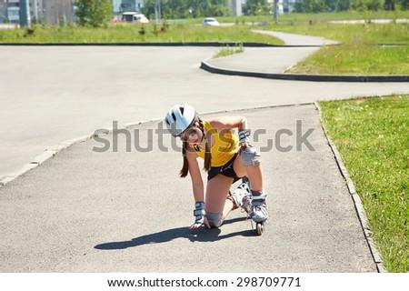 Little girl in helmet on the skates. sports child rollerskating in the city - stock photo