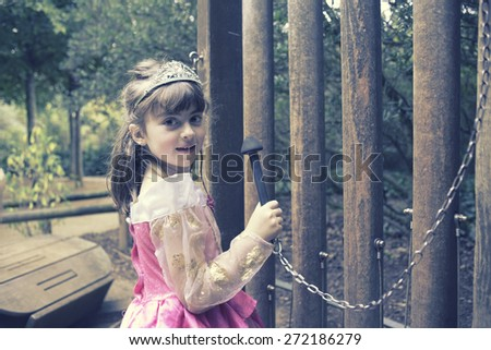 Little girl in her princess costume playing a giant xylophone - stock photo