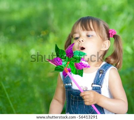 Little girl in jeans blowing on color propeller outdoor - stock photo