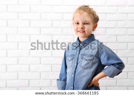Little girl in jeans suit on a white brick wall background