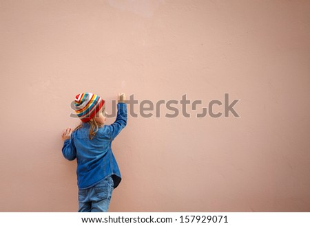 Little girl in jeans writing on the wall. Empty space for text or draw.
