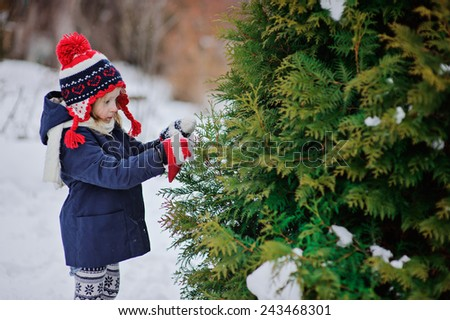 little girl in knitted red and blue hat decorating tree on the walk in winter garden - stock photo