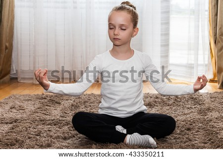 little girl in meditating position - stock photo