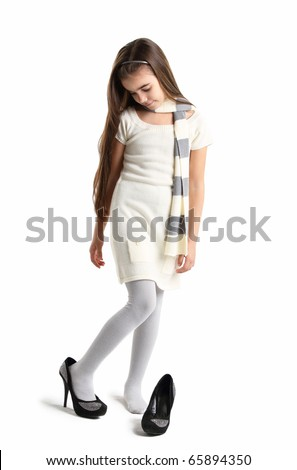 Little girl in mother's black shoes, isolated