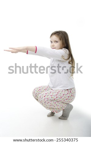 Little girl in nightwear warm-up isolated on white - stock photo