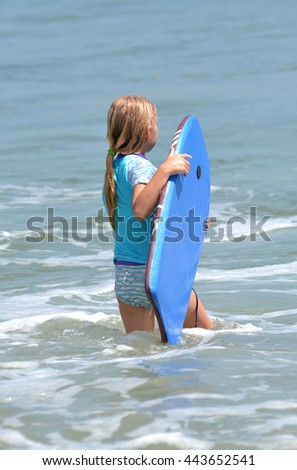 little girl in ocean water with board  - stock photo
