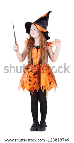 Little girl in orange costume of witch for Halloween holds and looks at wand isolated on white background. - stock photo