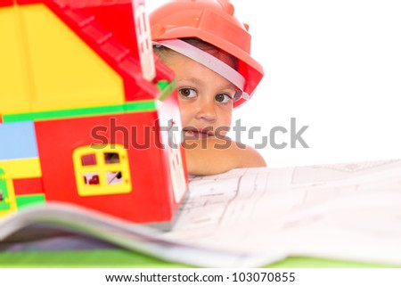 Little girl in orange helmet looking from behind the house - stock photo