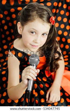 Little girl in orange peas dress with microphone - stock photo
