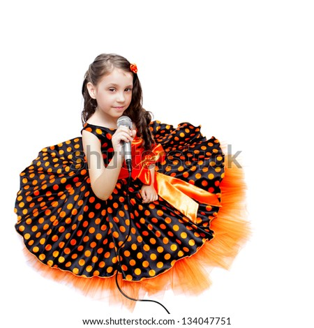 Little girl in orange peas dress with microphone isolated on white - stock photo