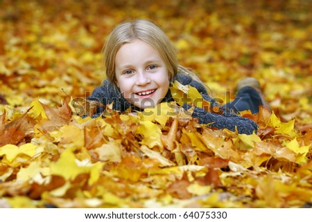 Little girl in pile of autumn leaves - stock photo