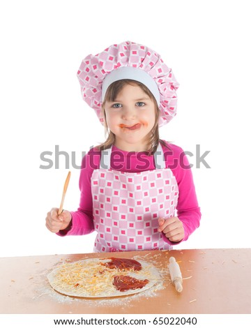 Little girl in pink apron licking tomato sauce from her face