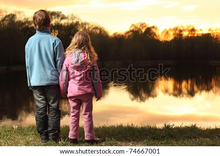 Little girl in pink clothes and boy in blue jacket holding hands and standing back on bank of river and admire on sunset - stock photo