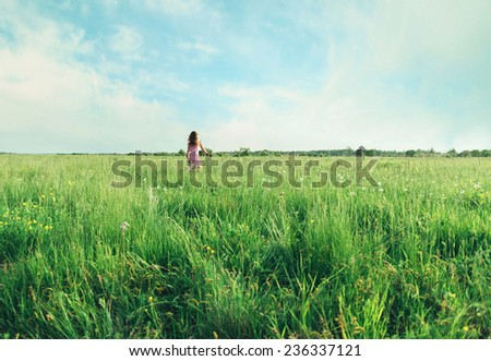 Little girl in pink dress running on summer green meadow, rear view - stock photo