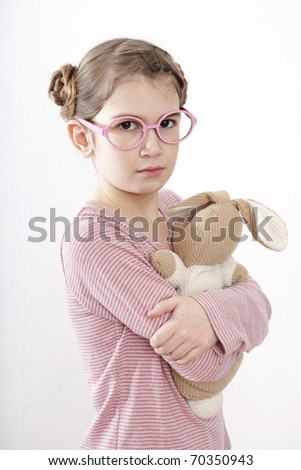 Little girl in pink glasses nine years old  hugging her loved toy